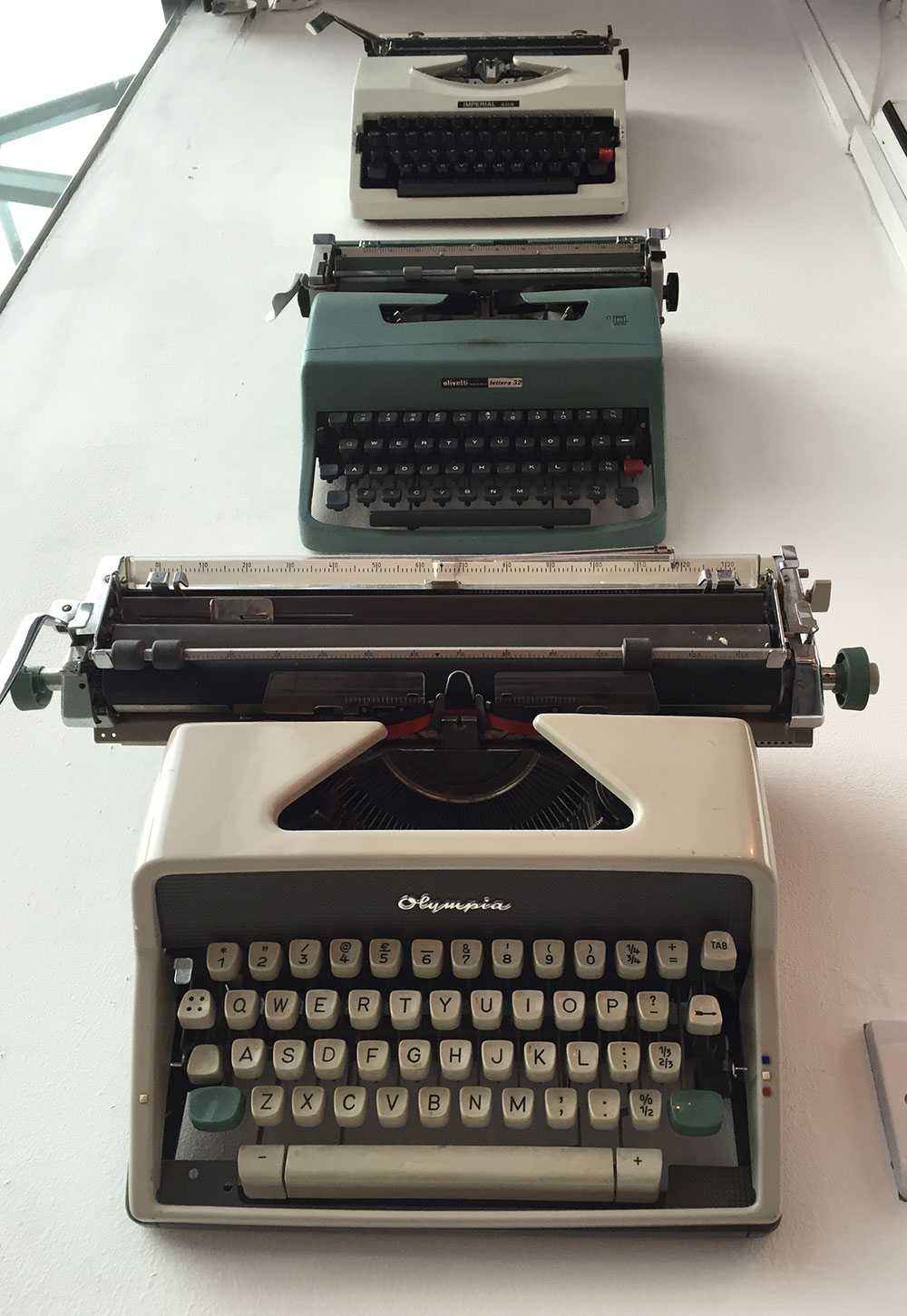 3 typewriters hanging on a wall
